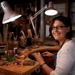 Shot of a happy young woman sitting at a workbench